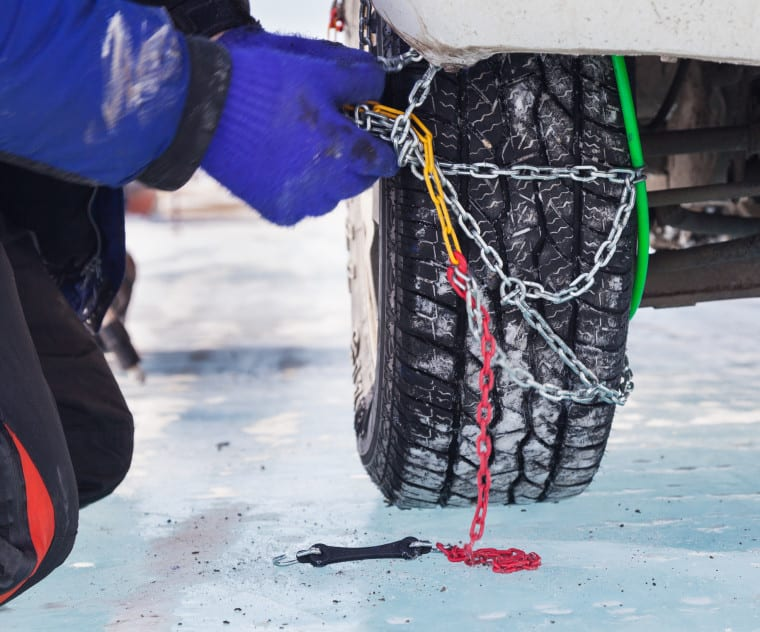 Man installing snow chain on car
