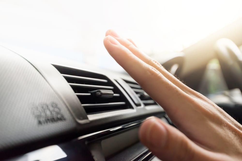 hand checking car air conditioning